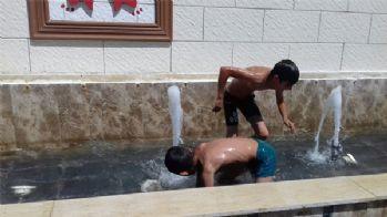 Sıcaktan bunalan çocuklar süs havuzunda serinledi